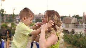 Menino bonito pequeno que beija sua mamã ao jogar no campo de jogos no parque video estoque