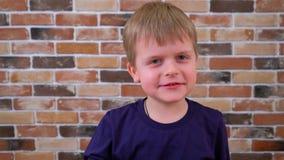 Menino bonito pequeno que come a filhós com um sorriso no fundo da parede de tijolo filme