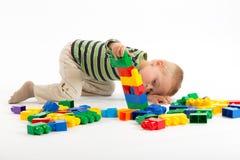 Menino bonito pequeno que joga com blocos de apartamentos Isolado no branco Imagens de Stock