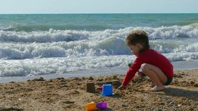 Menino bonito pequeno que joga na praia com areia vídeos de arquivo