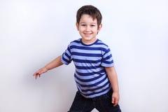 Menino bonito pequeno que sorri e que levanta, tiro do estúdio no branco Emo foto de stock