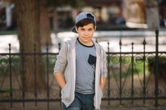 Menino bonito que anda na cidade Adolescente à moda fora fotografia de stock royalty free