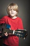 Menino bonito que aprende um instrumento Imagens de Stock Royalty Free