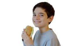 Menino bonito que come e que sorri Imagens de Stock