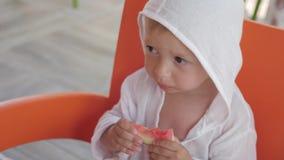 Menino bonito que come a melancia no café na praia video estoque