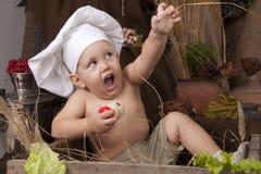Menino bonito que cozinha como um cozinheiro chefe Fotos de Stock