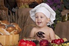 Menino bonito que cozinha no chapéu do cozinheiro chefe Foto de Stock Royalty Free