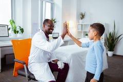 Menino bonito que dá altamente cinco ao pediatra profissional agradável fotografia de stock royalty free