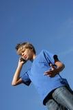 Menino bonito que discute em seu telefone de pilha Imagens de Stock Royalty Free