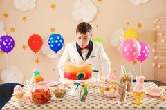 Menino bonito que funde para fora velas em seu bolo de aniversário dentro imagem de stock royalty free