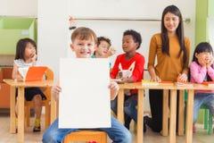 Menino bonito que guarda o cartaz branco vazio com a cara feliz na sala de aula do jardim de infância, conceito da educação do ja fotografia de stock