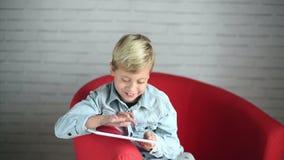Menino bonito que joga com um smartphone filme