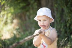 Menino bonito que joga com vara Fotos de Stock