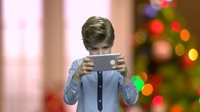 Menino bonito que joga o jogo em seu smartphone vídeos de arquivo