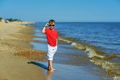 Menino bonito que levanta no beira-mar em um dia de ver?o imagem de stock royalty free