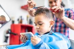 Menino bonito que obtém um corte do cabelo em Barber Shop Conceito da beleza imagem de stock