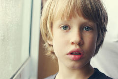 Menino bonito que olha através da janela Foto de Stock
