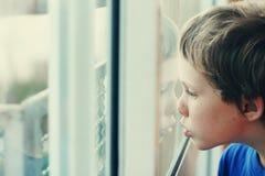 Menino bonito que olha através da janela Imagem de Stock