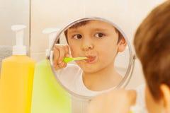 Menino bonito que olha no vidro e nos dentes de escovadela imagem de stock royalty free