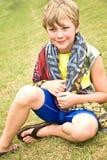 Menino bonito que senta-se na grama Imagens de Stock Royalty Free