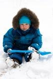 Menino bonito que senta-se na neve ao ar livre Imagens de Stock Royalty Free