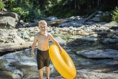 Menino bonito que tem o divertimento que monta um tubo inflável em um dia de verões fotografia de stock royalty free