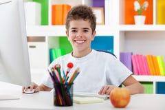 Menino bonito que usa um computador e um sorriso Imagens de Stock