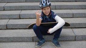 Menino branco com makng quebrado do braço o sinal da rocha filme