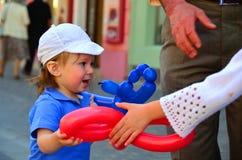 Menino branco feliz que recebe o presente do balão foto de stock