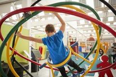Menino branco novo que usa o giroscópio humano, vista traseira foto de stock