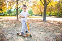 Menino brincalhão em um 'trotinette' fotografia de stock