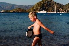 Menino bronzeado no mar no verão imagem de stock