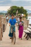 Menino burmese que monta sua bicicleta na ponte famosa de U-Bein em Amarapura perto de Mandalay, Myanmar Imagem de Stock Royalty Free