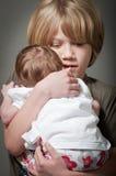 Menino calmo que guarda um bebê recém-nascido fotografia de stock
