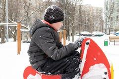 Menino cansado triste que senta-se em um campo de jogos nevado das crianças do inverno fotografia de stock royalty free