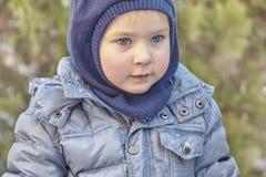 Menino caucasiano bonito do liittle com olhos azuis brilhantes grandes na roupa do inverno e na capa do chapéu no fundo verde Inf imagens de stock