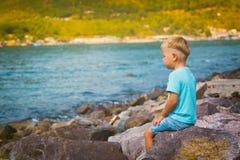 Menino caucasiano bonito que senta-se no beira-mar Fotografia de Stock