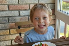 Menino caucasiano da criança de 5 anos feliz para comer para waffles vienenses do café da manhã com gelado e morangos fotos de stock royalty free