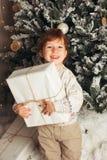 Menino caucasiano da criança nova que guarda o presente de Natal em Front Of Christmas Tree Menino de sorriso feliz bonito Foto v fotografia de stock royalty free