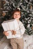 Menino caucasiano da criança nova que guarda o presente de Natal em Front Of Christmas Tree Menino de sorriso feliz bonito Foto v imagem de stock royalty free