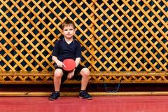 Menino caucasiano de sete anos no uniforme cinzento dos esportes que senta-se em um banco de madeira e que guarda uma raquete par fotos de stock royalty free