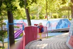 Menino caucasiano louro pequeno bonito, criança ou criança olhando através dos binóculos no campo de jogos fora imagem de stock royalty free