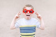 menino caucasiano louro que veste óculos de sol canadenses engraçados com folha de bordo Criança da criança que comemora o dia de foto de stock