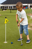 Menino caucasiano no mini campo de golfe Fotografia de Stock