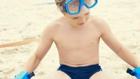 Menino caucasiano pequeno com mergulhar o equipamento que senta-se na areia na praia tropical e que joga com as aletas nas mãos imagem de stock