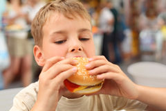 Menino caucasiano pequeno que come o hamburguer imagens de stock royalty free