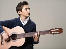 Menino caucasiano que joga na guitarra acústica Imagens de Stock