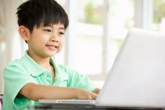 Menino chinês novo que usa o portátil em casa imagem de stock