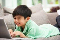 Menino chinês novo que usa o portátil que relaxa em casa fotos de stock royalty free