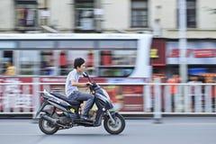 Menino chinês com o cão na motocicleta do gás Fotografia de Stock
